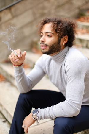 Upset mulatto male person sitting o steps with cigarette and smoking.  Young guy dressed in grey turtleneck sweater thinking about problems decisions and wears red string. Concept of autumn depression and bad habits.