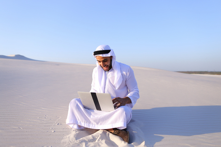 Successful young businessman male Muslim uses laptop to build drawing in Photoshop and prints fingers on laptop sitting on white sand in bottomless wide desert in afternoon against blue sky. Swarthy Muslim with short dark hair dressed in kandura, long, spacious dress made of white unpainted cotton with knitted lace cap of hafia, on top of which headscarf and dark brown shoes are tied. Concept of Arab and Muslim men, business and business, modern technology and gadgets, united Arab emirates and beautiful landscapes, sheikh in desert and seclusion from nature, national clothes of emirates.