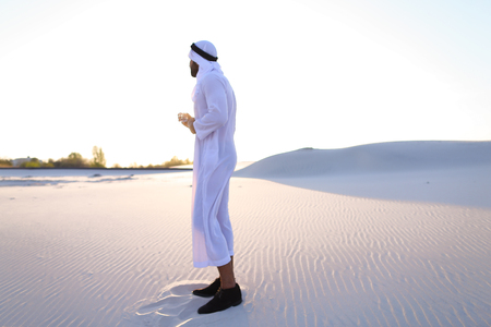 Stately Arab young man quenches thirst with glass of cool water and feels influx of strength and energy, smiles and looks to side, standing amidst endless sandy desert with pure white sand in open air on warm summer morning. Swarthy Muslim with short dark hair dressed in kandura, long, spacious dress made of white unpainted cotton with knitted lace cap of hafia, on top of which headscarf and dark brown shoes are tied. Concept of Arab and Muslim men, united Arab emirates and beautiful landscapes, hot climate and mineral water advertising, Emirates national clothes, good mood and happy emotions.