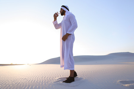 Stately Arab young man quenches thirst with glass of cool water and feels influx of strength and energy.