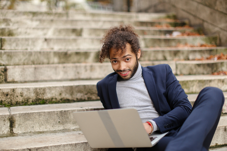 Personnel consultant typing message to client with laptop and lounging on steps with moss. Handsome man has long fleecy hair, beard and brown eyes. Concept of mediators between employers and job seekers, working with gadget outdoors. Stock Photo