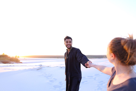 Pair of young lovers, male Muslim and woman of European appearance, look into each others eyes and hold hands, walking along wide, bottomless sandy desert. guy and girl are smiling and laughing in open air at sunset. woman with fair hair tied in tail dressed in light t-shirt and blue jeans, dark man with short dark hair dressed in black kandura, long spacious dress made of dark cotton and dark brown shoes. Concept of love will save world, variety of nationalities and culture, good mood and positive emotions.