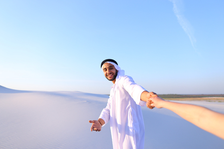 Cheerful Arab male with kindly smile on face leads womans arm from camera and shows desert landscapes, conducts outing in middle of bottomless sandy desert with white clean sand against blue sky in open air.