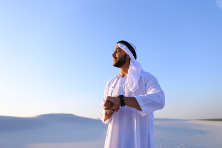 Attractive guy, emirate businessman uses for business and for work iWatch, who are put on hand, smiling and examining landscapes of large sandy desert against blue sky on hot summer morning. Swarthy Muslim with short dark hair dressed in kandura, long, spacious dress made of white unpainted cotton with knitted lace cap of hafia, on top of which headscarf and dark brown shoes are tied. Concept of Arab and Muslim men, business and business, modern technology and gadgets, united Arab emirates and beautiful landscapes, sheikh in desert and seclusion from nature, national clothing of emirates.