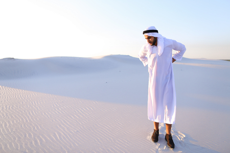 Frustrated fellow emirate suffers from back pain and holds on to waist.