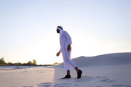 Attractive young sheikh with smile on face looks into camera and goes forward, stops and takes off glasses, enjoys and shows expanses of bottomless desert with white clean sand and clear blue sky on summer evening.