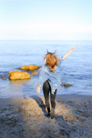 Sweet woman walks and poses in camera, smiles and laughs widely, raises hands up and starts happily whirling on spot, taking off jacket from shoulders. Stock Photo