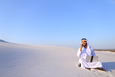 Modern male Arab and builder dials on cellular customer to clarify stages of construction and sits with computer on white clean sand outdoors on hot summer day.