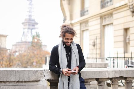 Handsome mulatto guy typing apologetic message to girlfriend by smartphone and listening to music with white earphones near Eiffel tower. Young boy wears fashion clothes. Concept of social networks, online communication, fast Internet.