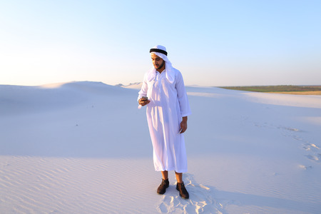 Arab young sheikh calls to friend or business partner and with smile on face and joy in eyes tells about winnings and amount of money in hands, rejoices and recounts bills standing in middle of bottomless desert with white sand on sunny summer day.