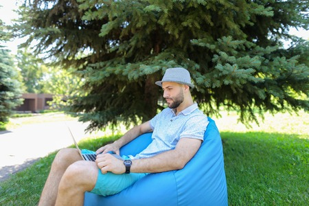 Gladden man watching live stream game and rejoicing favorite sport squad victory. Young guy dressed in grey t shirt and hat sitting in bag chair near spruce. Concept of using fast Internet for enjoying online matches for making bets on bookmaker sites.