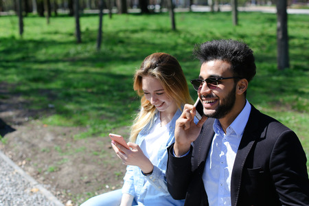 Lady has beautiful long hair and dressed in denim shirt, white T-shirt. Good looking man has beard, short hair and dimples on cheeks. Concept of traveling good camera modern technology