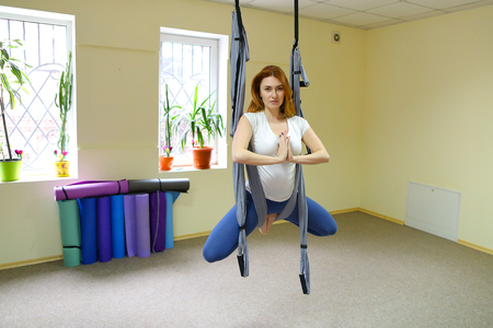 Beautiful girl of American appearance performs acrobatic elements in air, child concentrates and calmly holds on acrobatic ropes. Banco de Imagens