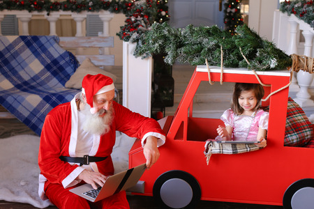 Father Christmas writing letters on laptop. Beautiful princess enjoying with presented tablet. Concept of using modern gadgets and reveling in Christmas spirit.