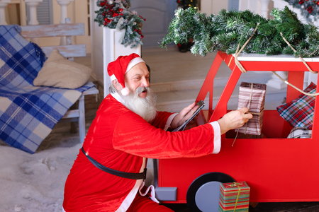 Father Christmas sitting near red children car in front of decorated house and using tablet. Man playing role of Santa Claus. Concept of holiday magic moments.