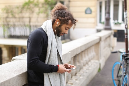 Handsome mulatto guy typing apologetic message to girlfriend by smartphone and listening to music with white earphones near Eiffel tower. Stock Photo