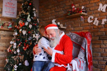 Gelukkig mannelijk kind rent naar de kerstman en knuffel hem Stockfoto