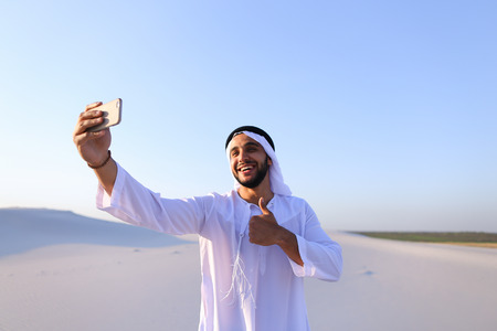 A happy, handsome Arab guy, making a video call smiling and showing the beautiful views and sights of large sandy desert outdoors on a summer day Stock Photo