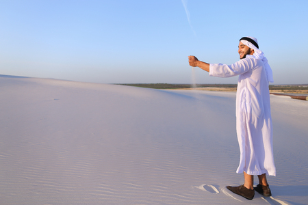 Young Arab guy who takes sand in hand and lifts it to smiling face 스톡 콘텐츠