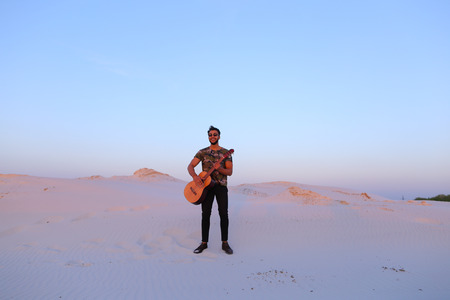Young Muslim man stands at full length and plays melody on stringed musical instrument Banco de Imagens