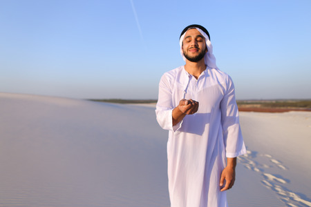 Young Arab guy who takes sand in hand and lifts it to smiling face and blows through fingers fine white grains