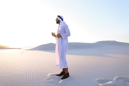 Stately Arab young man quenches thirst with glass of cool water and feels influx of strength and energy