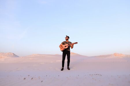 Young Muslim male performer and singer walks through sandy desert with guitar in hands