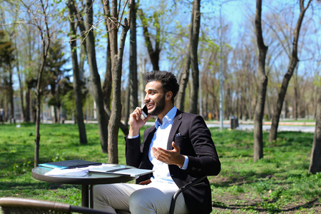 Handsome person using laptop and clicking keyboard, putting hands up. Male has beard, short hair and dimples on cheeks. Guy dressed in black jacket and blue shirt. Concept of modern technologies new apps on laptop online selling.
