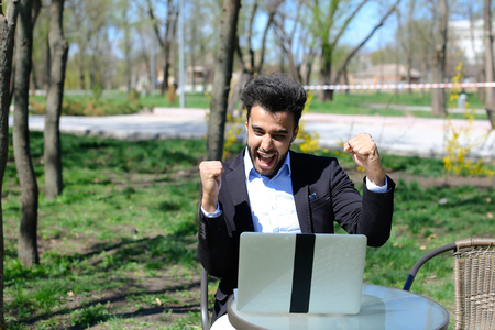Person using laptop and clicking keyboard, putting hands up, close computer and goes away. Boy has beard and short hair. Guy dressed in black jacket, white jeans and blue shirt. Concept of modern technologies new apps on laptop online work for freelancer. Stock Photo