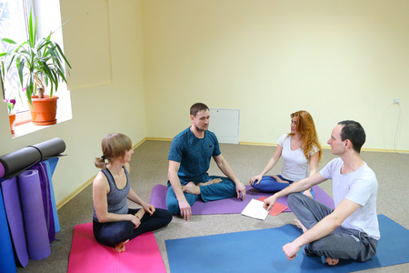 Four young people of American appearance sit on floor at fitness studio and discuss plans for joint weekend. Friends smile fun, dressed in comfortable sports pants and t shirts, next to wall folded drawn mats of different colors. Concept of importance of spending time with loved ones, common interests and preferences bring people together.