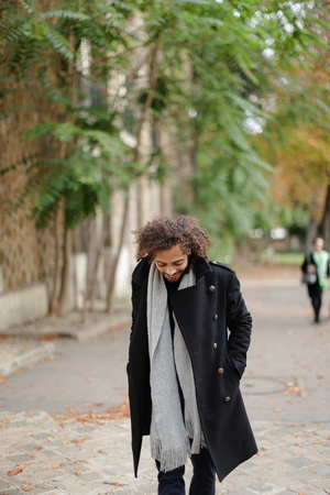 Handsome half Nigerian guy strolling outside. Attractive boy wears black coat and grey scarf. Concept of walking young male person and free time.