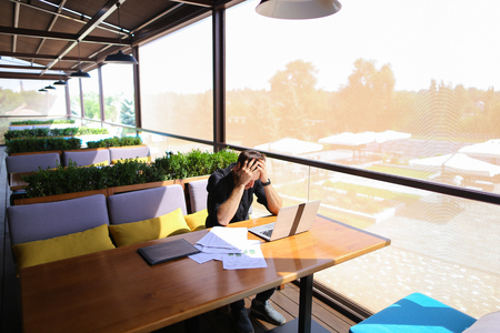 Freelance copywriter typing text fast on laptop keyboard at cafe table and looking tired. Handsome young man dressed in black shirt has dark hair and beard. Concept of typewriting skills and independent contractor for agencies. Stock Photo