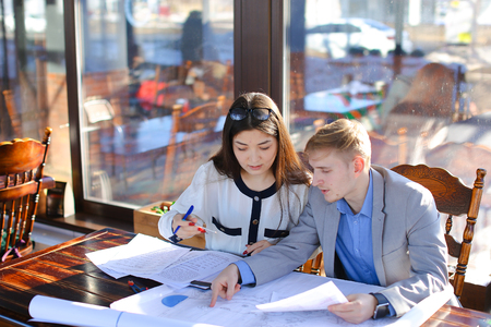 Students calling professor by smartphone to ask about architecture project. Boy and girl drawing with divider and ruler at cafe. Concept of preparing home task and drafting. Stockfoto