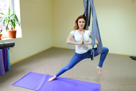 Beautiful girl of American appearance performs acrobatic elements in air, child concentrates and calmly holds on acrobatic ropes Banco de Imagens - 95046322