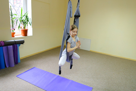 child concentrates and calmly holds on acrobatic ropes.