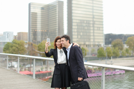 Marketer  and HR manager  taking selfie by smartphone, old friends suddenly meet during lunch break. Middle-aged American male and female wearing strict suits smiling. Concept of innovative technologies and gadgets, making photos with mobile or fashionable clothes.