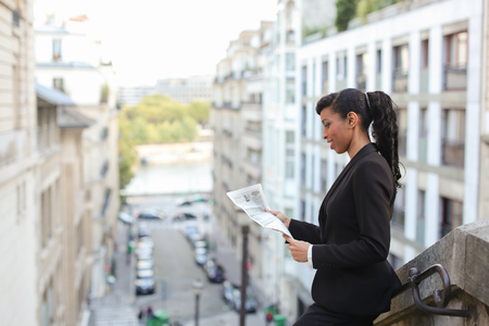 Half African girl reading newspaper near high building with close up of face. Charming woman looks gladden and confident. Stock Photo