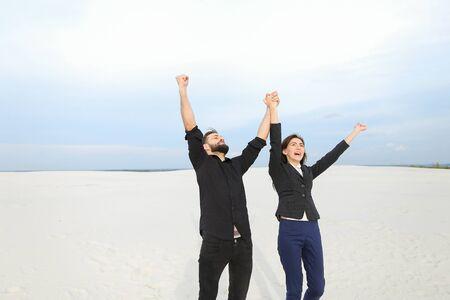 モデルの男女が写真撮影のために海辺に来て、若者は砂の中で喜びのためにジャンプします。 写真素材