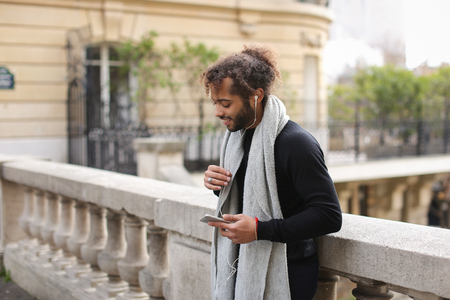 Handsome mulatto guy typing apologetic message to girlfriend by smartphone. Stock Photo