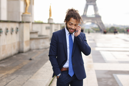 Happy young boy having fun and talking with friend with smartphone near Eiffel Tower in background. Gladden man enjoying with travelling France and visiting famous places. Concept of cheap calls and c