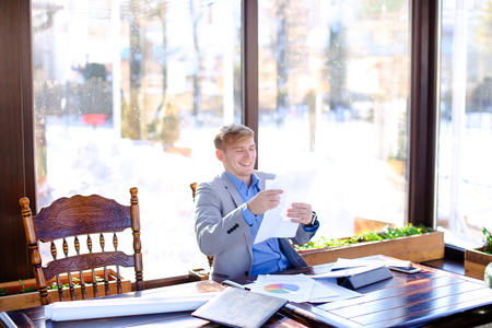 Hardworking student preparing before exam in fast motion at cafe with papers and typing by tablet in fast motion. Young guy wears smart watch and grey suit. Concept of preparing before exam using gadgets and document.