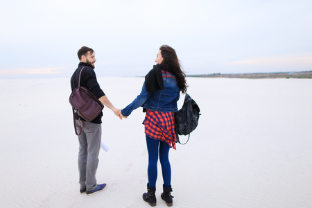 girlfriend and boyfriend walking in deserted place, couple holding hands go to joint photoshoot. Young people with backpacks in everyday clothes look at each other. Concept of beautiful landscapes, stylish accessories or fashionable outfits.