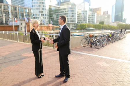 Male financial manager talking with employees outdoors. Concept of conversation with boss and decision making. Man in dark suit speaking with team members. Stock Photo