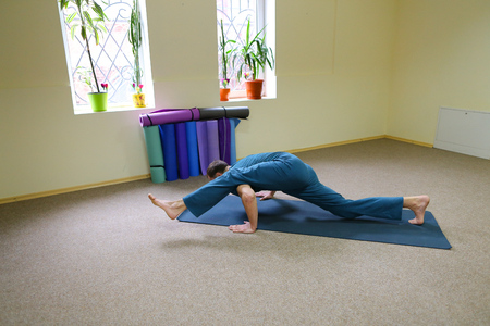 Beautiful dark-haired man performs asanas from yoga, guy sitting in room on floor on fitness mat. Inside spacious and bright, walls painted in nice yellow color, on windowsills pots with flowers. Concept of importance of keeping body in good shape, exercise and develop spiritually.