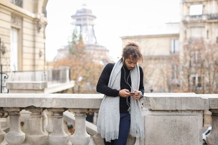 Handsome half Nigerian guy chatting by smartphone with girlfriend and using white earphones near Eiffel tower. Young male person wears black sweater and grey scarf, has fleecy hair and beard. Concept of listening to music and Internet communication.