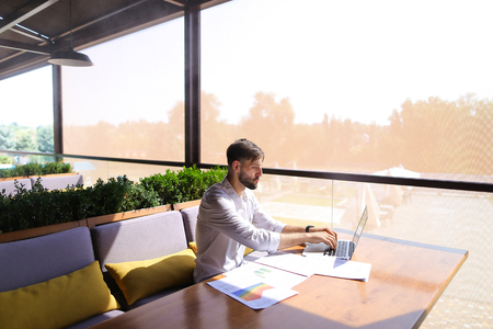 Intelligent American financier working with diagrams and documents at table indoors near green room plants. Clever young man wears classic style white shirt. Concept of  person concerned with the management of large amounts of money on behalf large organizations and using modern technologies.