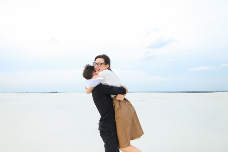 future lawyers male and female come to seaside to have rest after passing exams, girl with ponytail in glasses tell good news friend bearded man with short fair hair. Young people wearing stylish outfits dancing for joy.