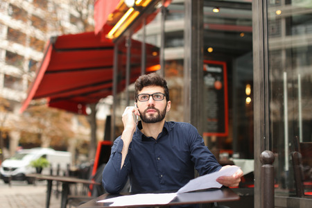 Real estate agent talking with disgruntled client by smartphone at cafe table