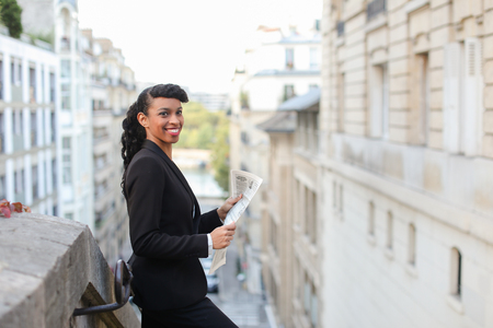 Young reporter looking at cam with newspaper on balcony near high building. Pretty woman looks successful and has ponytail hairstyle and black fleecy hair. Concept of working correspondent and writing articles. Imagens