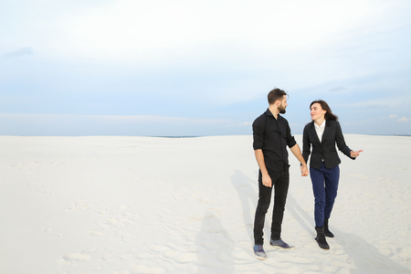Marketers male and female stop by seaside after last working day before vacation, young people rejoicing at beginning of rest. Bearded guy and fair-haired girl dancing among sands. Concept of fashionable clothes, stylish outfits or modern accessories.